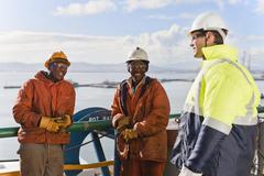 Workers talking on oil rig Stock Photos