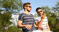 Two guys best friends are sitting on fencing, talking and laghing Stock Footage