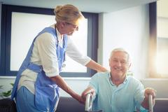 Female doctor helping senior man to walk with walker - stock photo
