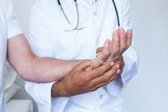 Male doctor giving palm acupressure treatment to the patient - stock photo