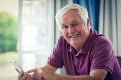 Portrait of senior man using mobile phone at home Stock Photos