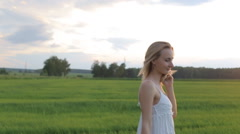 beautiful woman walking in the field with a bouquet of flowers - stock footage