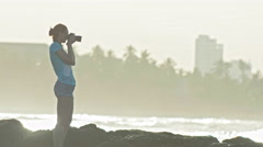 Young woman with red hair in glasses photographs sea-life and the coast on the - stock footage