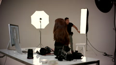 Female photographer working with assistant at studio. Stock Footage