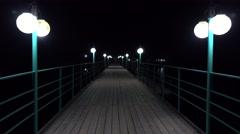 Empty lit pier at night 4K shot Stock Footage