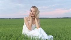 Cute young woman speaking on a mobile phone on the grass Stock Footage