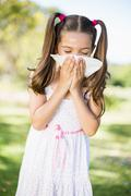 Girl blowing her nose with handkerchief while sneezing Stock Photos