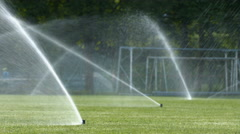 Lawn sprinklers. Pouring water on a sport field - stock footage