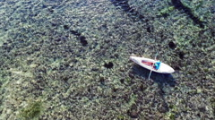 Young lady paddling the kayak in the sea with lots of splashes - stock footage