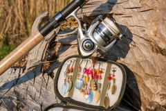 Fishing rod with reel and various kind of baits on the natural background. - stock photo