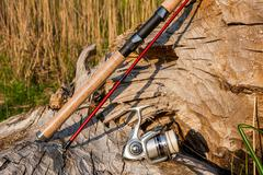 Fishing rod and reel on the natural background. - stock photo
