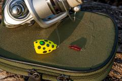 Fishing reel and various kind of baits on the natural background. - stock photo