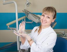 beautiful blonde woman dentist holding a medical instrument. dental equipment in - stock photo