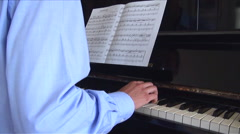 Young man playing the piano, with sheet music Stock Footage