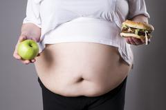 Women suffer from obesity with big hamburger and apple in hands. Jun - stock photo