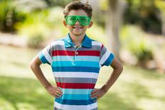 Young boy in shutter shades standing with hand on hip - stock photo