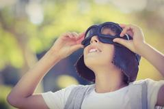 Boy in aviator goggles looking up - stock photo