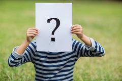 Boy covering his face with a placard that shows question mark sign - stock photo
