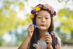 Girl blowing bubble wand - stock photo