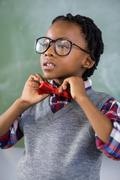 Thoughtful schoolboy adjusting a bow tie in classroom - stock photo