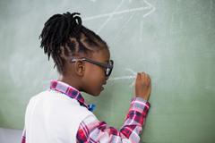 Schoolgirl doing mathematics on chalkboard in classroom - stock photo