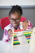 Schoolgirl using a maths abacus at school Stock Photos
