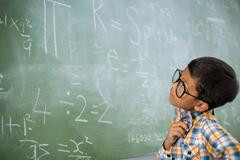 Thoughtful schoolboy looking at mathematical problem in classroom - stock photo