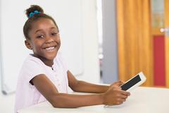 Smiling schoolgirl using digital tablet in classroom at school - stock photo