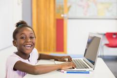 Smiling schoolgirl using laptop in classroom Stock Photos