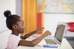 Schoolgirl using laptop in classroom Stock Photos