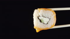 A sushi by chopsticks on a black background Stock Footage