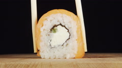 CLOSE UP: Human hand takes a sushi by chopsticks - stock footage
