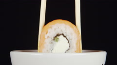 CLOSE UP: Human hand dips a sushi by chopsticks Stock Footage