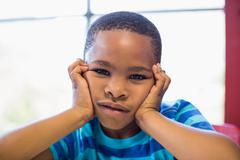 Upset boy sitting in classroom - stock photo