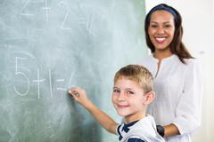 Portrait of teacher assisting boy in doing addition on chalkboard Stock Photos