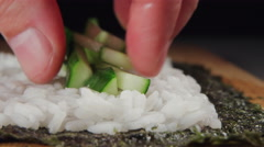 Sushi chef's puts a sliced cucumber on a white rice Stock Footage