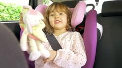 Happy baby girl sitting in car singing hugging plush toy 4K Stock Footage
