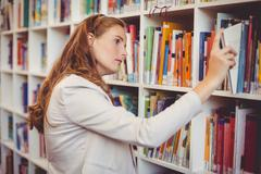 School teacher selecting a book from bookcase in library Stock Photos