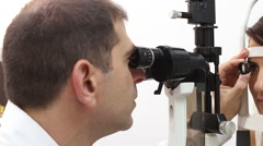 An optometrist with a slit lamp machine Stock Footage
