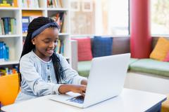 Schoolgirl using laptop in library - stock photo