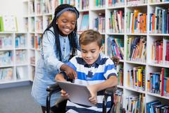Happy schoolgirl standing with schoolboy on wheelchair using digital tablet - stock photo