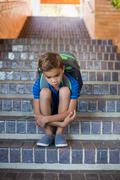 Sad schoolboy sitting alone on staircase - stock photo