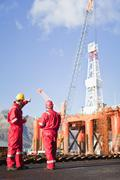 Workers talking on oil rig - stock photo
