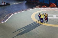 Workers talking on helipad of oil rig Stock Photos