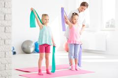 Two smiling little girls having a physical therapy session with a female PT Stock Photos