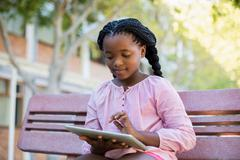Schoolgirl sitting on bench and using digital tablet in campus - stock photo