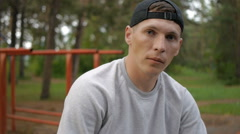 Portrait of handsome young man with cap in forest Stock Footage