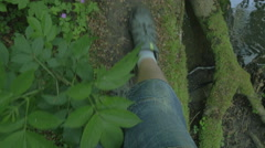 Feet walking over treetrunk point of view over water Mountain climing shoos 4 - stock footage