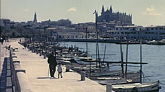 Palma, Majorca 1969: child walking in front of the port with his grandfather Stock Footage