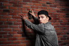 Graffiti man in cap spraying brick wall by aerosol can - stock photo